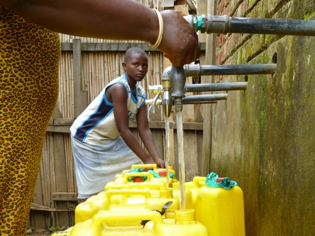 Young Black Child Filling Water Jugs